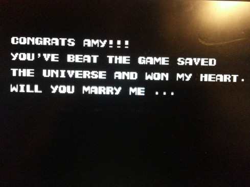 """E finalmente o pedido, na tela do encerramento do jogo: """"Parabéns Amy!! Você zerou o jogo, salvou o universo e conquistou o meu coração. Quer se casar comigo..."""""""